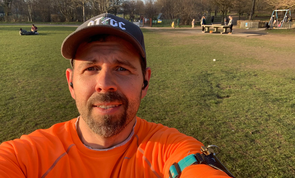 Man with orange sports top in open park
